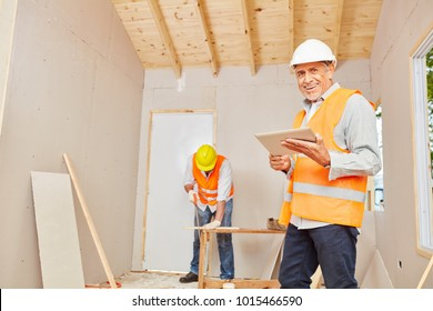 Experienced craftsman with carpenter at construction site
