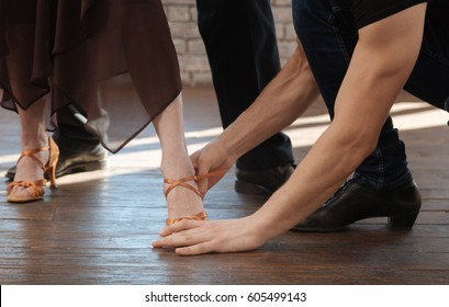 Experienced dance couch teaching aging couple tango in the ballroom