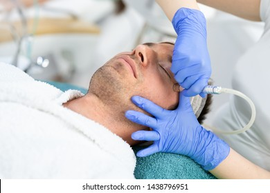Experienced dermatologist is undergoing anti-aging ultrasound procedure at wellness center. Man is lying. His eyes are closed with pleasure
