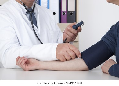 Experienced Doctor measures blood pressure