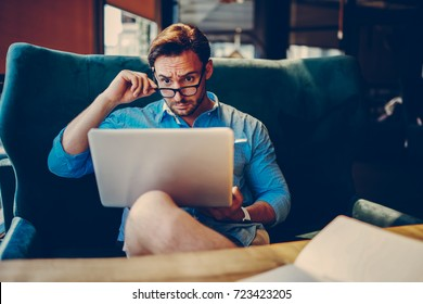 Experienced entrepreneur confused with financial news doubting while reading information from networks.Skeptic businessman in eyeglasses angry about problems with project checking reports on laptop