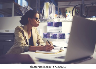 Experienced female administrative manager in trendy eyewear organizing financial documents for upcoming business meeting with executive using modern computer and wireless internet in office indoor
