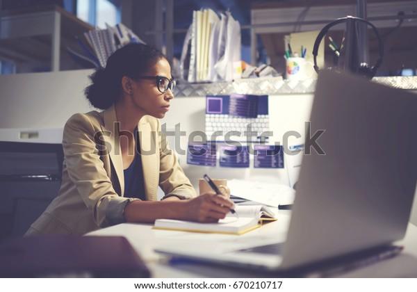 Berufserfahrene Verwaltungsdirektorin in trendigen Brillen, die Finanzdokumente für die bevorstehende Geschäftssitzung mit Geschäftsführerin mit modernem Computer und drahtlosem Internet im Büro im Indoorraum organisiert