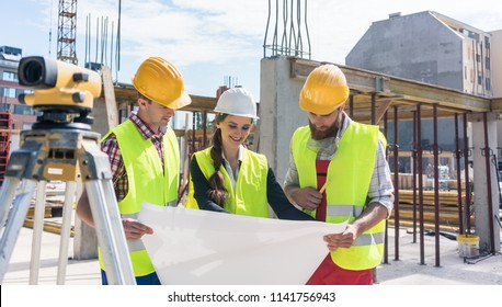 Experienced female architect smiling while analyzing a blueprint together with two workers outdoors on the construction site of a modern residential building