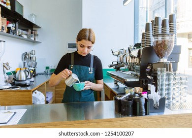 Experienced female barman making cappuccino. Woman barista in apron pouring hot milk foam into coffee. Latte art, small business and professional coffee brewing concept.