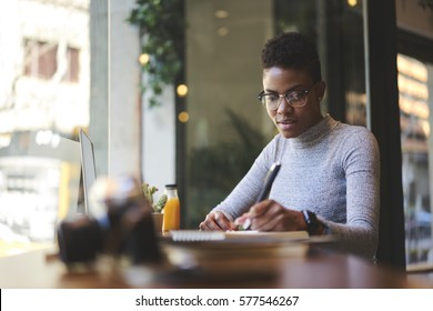Experienced female editor of fashion magazine working on creation of book review writing  best ideas into notebook before publishing on web page of issue online version sitting in modern cafe