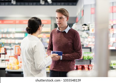 Experienced female pharmacist checking the indications and contraindications of a new medicine next to a young male customer in a modern pharmacy