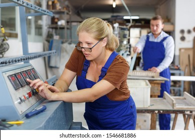 Experienced female worker of glass factory engaged in adjustment of glass chamfering machine