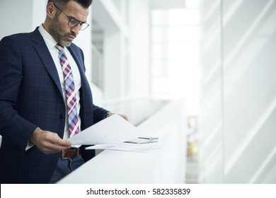 Experienced financier of business enterprise dressed in elegant formal outfit and glasses reading documentation and reports preparing speech on conference meeting with leaders and chief executive