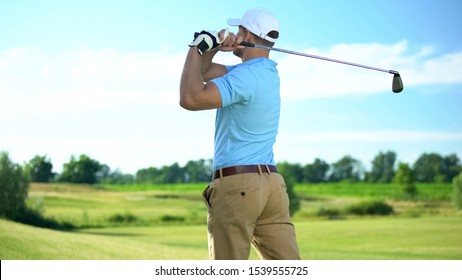 Experienced golf player hitting ball in draw position at course, back view