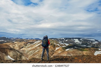 Experienced hiker woman with heavy huge backpack standing and looking at rhyolite mountains Landmannalaugar Iceland Beautiful inspirational landscape, trekking and activity.