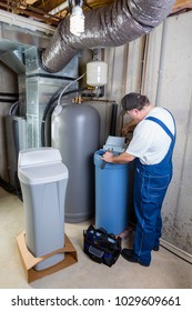 Experienced home installer fixing issues encountered on a new water softener tank that he is installing using his tools in a utility room in a basement