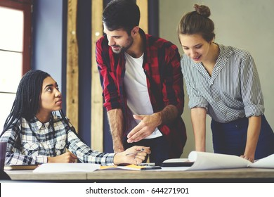 Experienced male coach explaining to employee solution of correcting her mistakes in graphic plan of design interior, professional partners cooperating during working session in coworking office