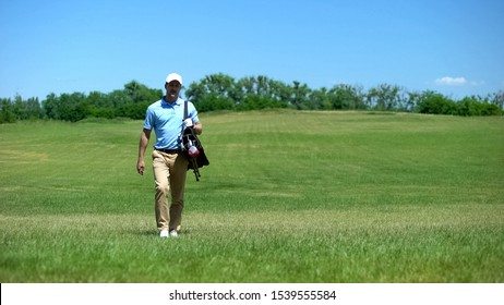 Experienced male coach moving on course with golf clubs bag, recreational hobby