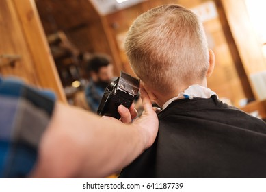 Experienced male hairdresser working with hair cutting machine