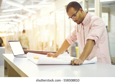 Experienced male interior designer in trendy eyewear correcting mistakes in project planning drawing new layout working in office using laptop computer and wireless connection tofast 4G internet