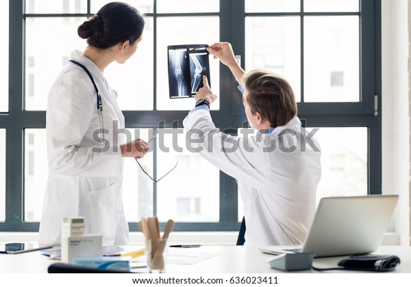 Experienced male orthopedist helping his female colleague with the interpretation of an X-ray of the knee of a patient in the office