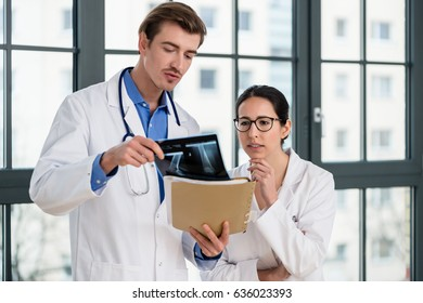Experienced male physician and his female colleague interpreting the radiograph of the knee of a patient in a modern orthopedic clinic
