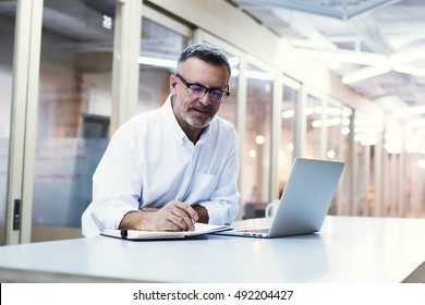 Experienced male skilled economist writing notes for delegate projects to his subordinates. University professor in eye glasses prepare for lectures after reading electronic book on laptop computer
