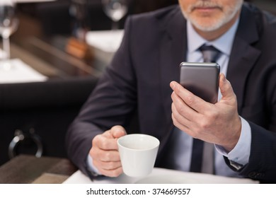 Experienced mature businessman is waiting for his business partner in cafe. He is drinking coffee and using a mobile phone. The man is sitting at the table with confidence