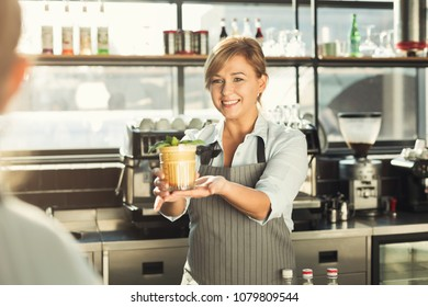 Experienced middle aged barista giving tasty cold coffee non-alcoholic cocktail to customer. Bartender at her working place. Small business concept, copy space