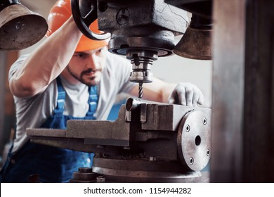 Experienced operator in a hard hat. Metalworking industry concept professional engineer metalworker operating CNC milling machine center in manufacturing workshop.
