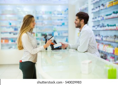Experienced pharmacist counseling female customer in modern pharmacy, and woman pay with credit card