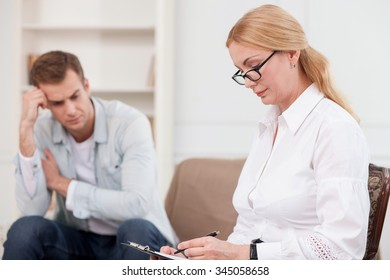 Experienced psychologist is consulting young man. She is sitting on sofa and writing with seriousness. The man is crying and looking down with depression