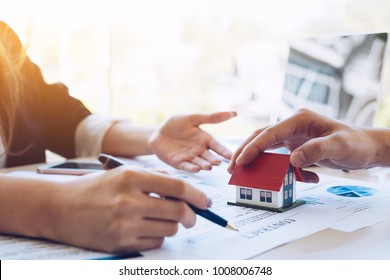 experienced real estate agent showing house model to client and ready to sign contract