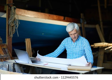 Experienced shipbuilding engineer looking at sketch on unfolded blueprint by his workplace