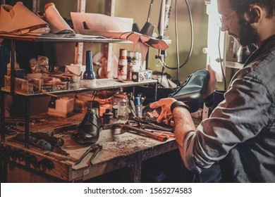 Experienced shoemaker is creating retro leather shoes at his comfortable workshop.