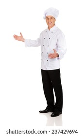 Experienced smiling chef holding empty space in hands