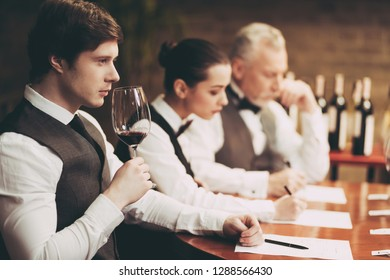 Experienced sommelier explores taste of wine in restaurant. Young waiter tastes alcoholic beverages. Checking taste, color, sediments of wine