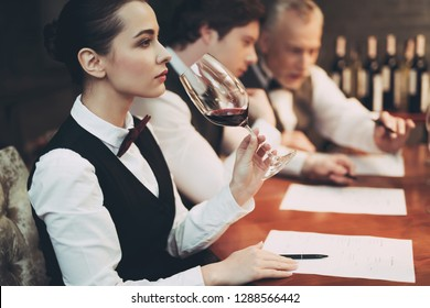 Experienced sommelier woman explores taste of wine in restaurant. Wine tasting. Checking taste, color, sediments of wine