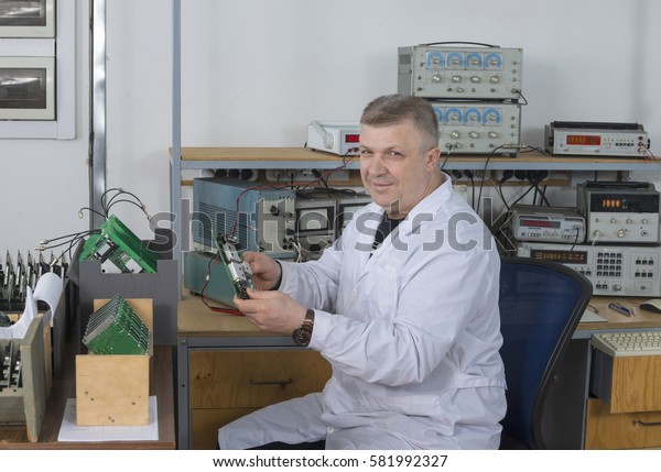 Experienced   specialist   checks   the   quality   of   printed   circuit   boards