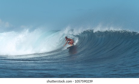 Experienced surfer rides a big crystal clear barrel wave on popular surf spot. Awesome male surfboarder carves a big deep blue wave coming from the powerful ocean. Adrenaline filled summer activity.
