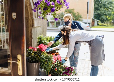 Experienced woman florist helping female client to choose potted plant in flower shop.Females owner of floral shop and consumer inprotective masks in faces.Lockdown, quarantine, back to normal concept