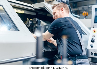 Experienced worker changing tool setup of lathe machine on the factory floor