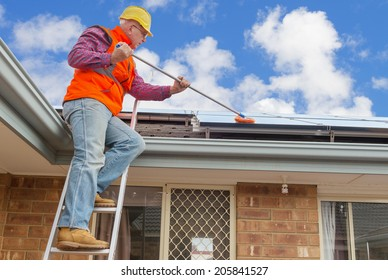 experienced worker cleaning solar panels on house roof