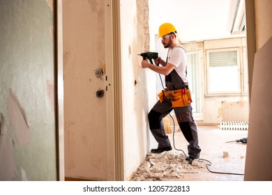 Experienced worker using hammer drill for tearing down a wall structure