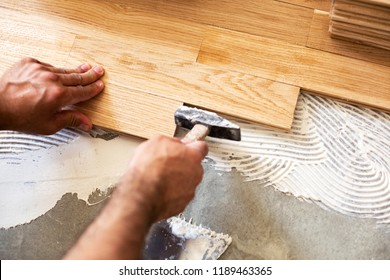 Experienced worker   using  hammer for parquet alignment and dimensional stability of the floor surface