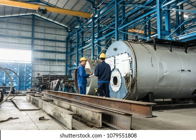 Experienced worker writing observations while checking the quality of manufactured industrial boilers