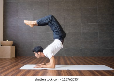 Experienced yogi doing scorpion yoga pose in gym. Man looking at camera and practicing yoga. Yogi concept. Side view.