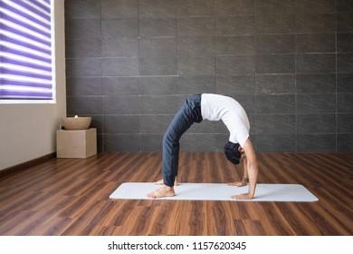 Experienced yogi doing wheel yoga pose in gym. Man practicing yoga. Yogi concept. Side view.