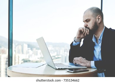 Experienced young businessman looking stressed and tired while sitting at his office desk with laptop computer. Young male economist reading financial news on net-book about falling shares on exchange