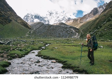 Experienced young woman tourist with backpack admiring amazing scenery of Salkantay mountain during hiking trekking on weekend.Female traveler with stick enjoying wanderlust in Peru