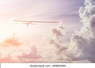 Experimental aircraft on sun energy. Solar Impulse in cloudy sky with sunlight