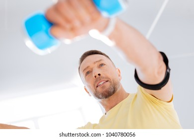 Experimenting with biohacking. Low angle of appealing charming confident man elevating dumbbell while looking straight and exercising