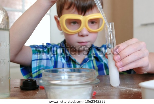 Experiments on chemistry at home. Boy Pour the water to test tube using pipette.