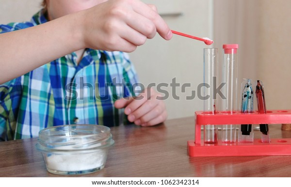 Experiments on chemistry at home. Boy conducts a chemical reaction in a test tube.